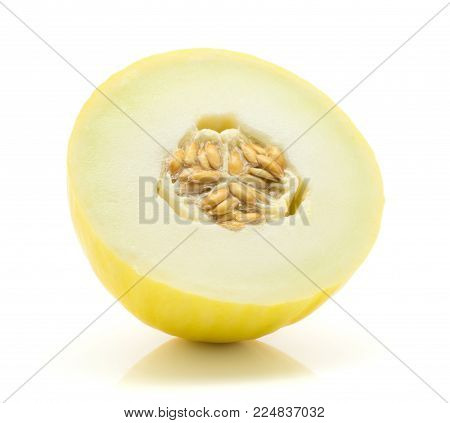 Yellow honeydew melon half with seeds isolated on white background
