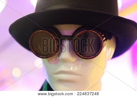 steampunk, head of a male display dummy wearing a carnival costume with steampunk glasses and a black hat