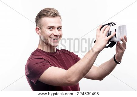 Excited gamer. Upbeat fair-haired young man in a burgundy t-shirt being about to put on a VR headset and smiling at the camera happily while posing against a white background