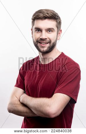 Great mood. Upbeat young man folding his arms across his chest and smiling at the camera while posing isolated on a white background