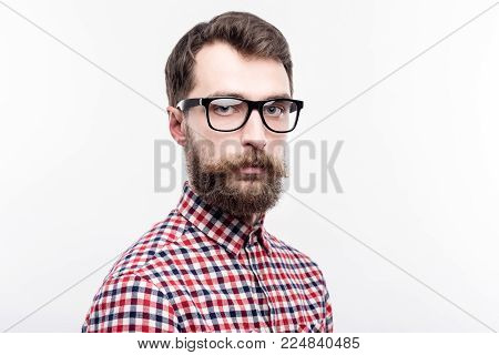Serious attitude. The portrait of a handsome bearded man in eye glasses standing half-turned and looking at the camera with a serious expression