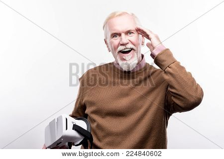 Mind-blowing technologies. Upbeat elderly man touching his head, being pleasantly surprised, having used a virtual reality headset for the first time