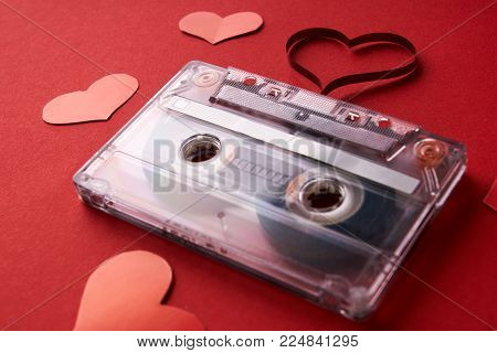 Audio cassette with magnetic tape in shape of heart and red hearts on red background, close-up. Valentines day holiday and love music concept