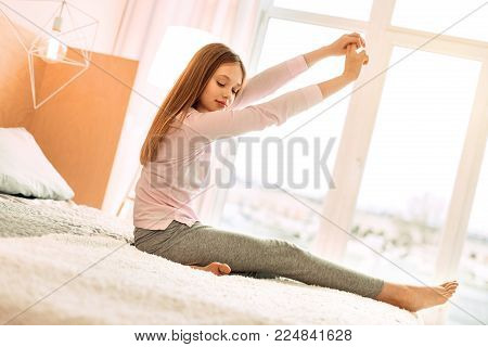 Supple body. Charming teenage girl sitting on the bed and stretching herself in the morning having woken up in the morning