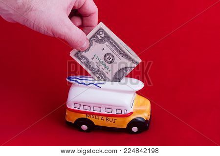 money box, in the form of a ceramic bus with a denomination of two dollars, on a red background. The concept of saving money. Accumulation for rest