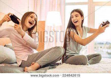 Full of emotions. Pretty teenage sisters sitting on the bed in their room, playing video games with the controllers and smiling brightly, being really emotional