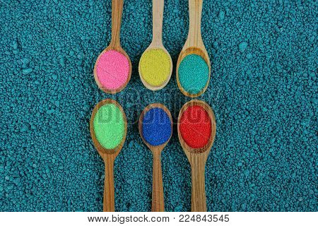 a row of wooden spoons with colored powder on a blue background