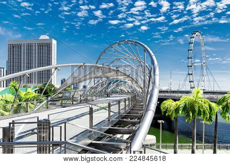 Singapore city landscape at day blue sky. Pedestrian DNA bridge and ferris wheel Flyer at Marina Bay view. Urban cityscape