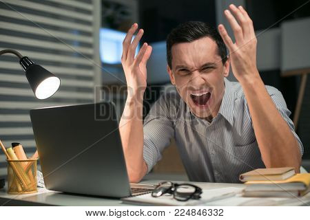 Nervous breakdown. Stressful skillful male employee gesturing while squalling and sitting at the table