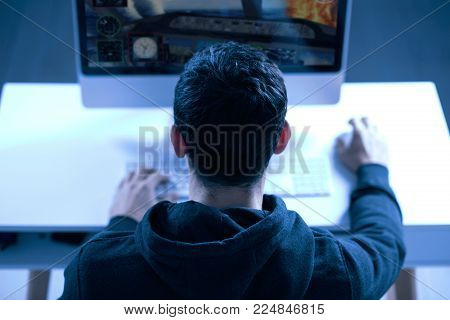 New level. Top view of confident strong male gamer sitting with back to the camera while completing level and putting hands on keyboard and mouse