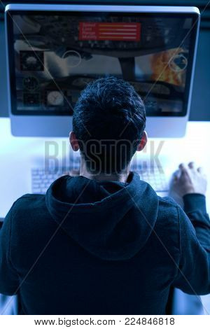 Do not stop. Top view of back of young male gamer staring at the screen while sitting and playing game