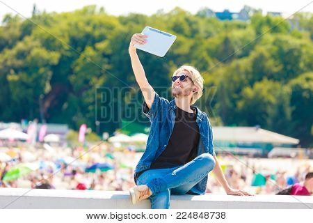 Contacts, technology, self-esteem concept. Young blonde man on vacations using his tablet to take cool selfie shot