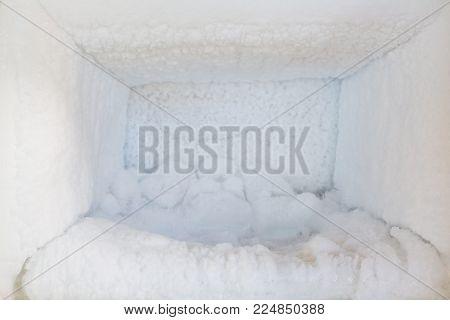 Empty of a refrigerator. Ice buildup inside of a freezer walls.