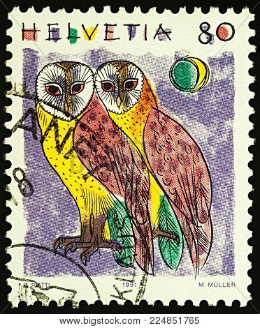 Moscow, Russia - February 02, 2018: A stamp printed in Switzerland shows two sitting Barn Owls (Tyto alba), series