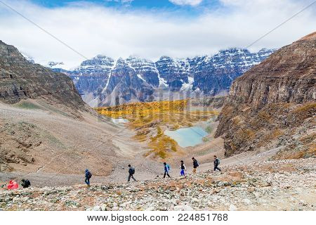 LAKE LOUISE, CANADA - SEPT 17, 2016: Hikers traverse the rocky trail at Sentinel Pass in the Larch Valley near Lake Louise in Banff National Park, Alberta, with snow-capped Valley of Ten Peaks in the background and Larch trees around Minnestimma Lakes in