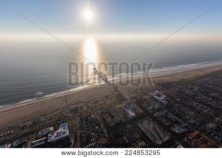 Aerial view of pacific coast fog with afternoon sun at Huntington Beach Pier in scenic Orange County California.