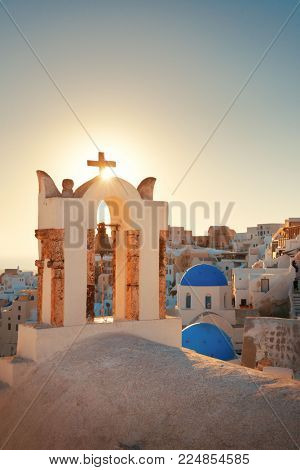 Santorini skyline sunset with church bell and buildings in Greece.