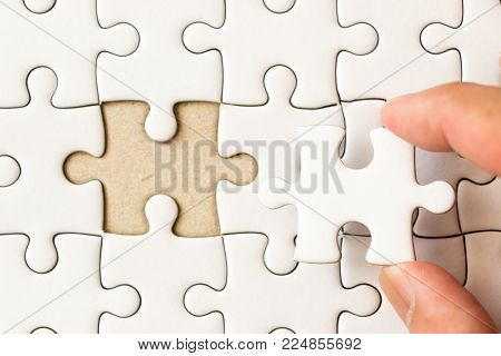 Closed up background of white plain jigsaw with hand that hold missing piece to match or fulfill