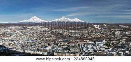 Wintery panorama of top view of urban landscape residential buildings of Petropavlovsk-Kamchatsky City and scenery volcanoes of Kamchatka Peninsula: Koryak Volcano, Avacha Volcano, Kozelsky Volcano. Eurasia, Russian Far East. poster