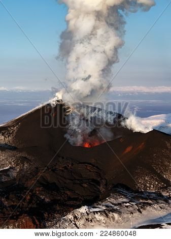 Stunning scenery eruption volcano landscape of Kamchatka Peninsula: aerial view of active Tolbachik Volcano, erupting fountain of red hot lava from cinder cone of volcanic crater. Russian Far East, Kamchatka Region.