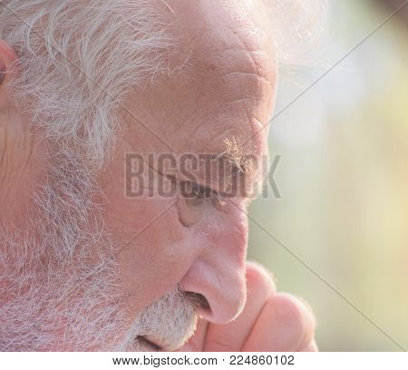 Old man thinking something,close-up portrait with pain, stress,old age man or old people concept-thinking or senior man suffering from headache with the light of sun at park with his hand at his head