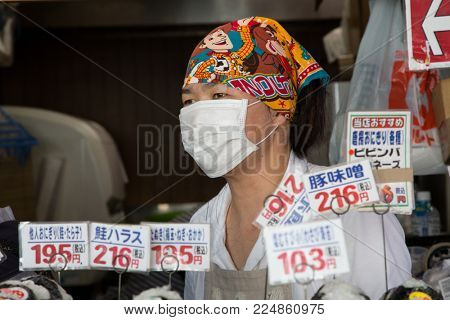 Tokyo, Japan - 26 June 2016: Young street vendor, wearing a customary surgical mask,  at a stall in Tsukiji street market in Tokyo. This is the biggest fish market in the world.