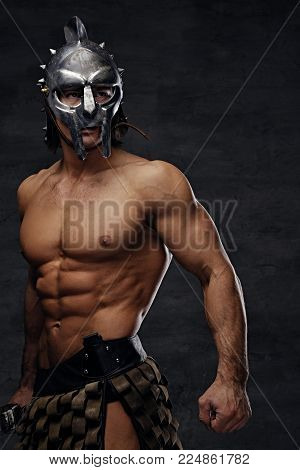 Shirtless athletic male in silver gladiator helmet posing on grey background.