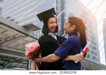 You did it. happy asian mother hug with flower and congratulation graduation to her caucasian daughter, family, education, proudly, degree certificate, congratulation ceremony and successful concept
