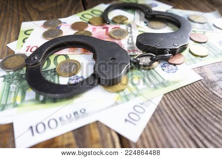 Handcuffs on a pile of euro banknotes. The symbolic meaning of economic crimes. Copy paste