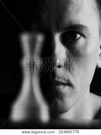 Portrait of young man playing chess, isolated on dark background, close-up. Playing chess concept