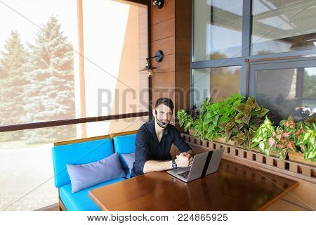 Educational consultant talking to student by laptop video call with headset microphone. Handsome serious man has beard and wears black shirt. Concept of assisting students in making decisions and giving advices in tuition fees, visa, and enrolling at High