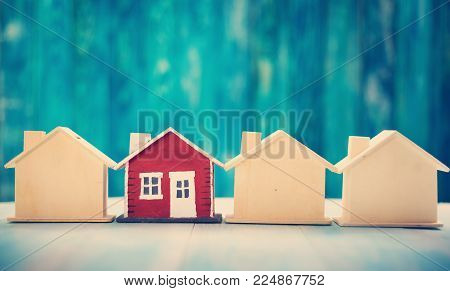 Red house model on blue wooden background. Property concept.