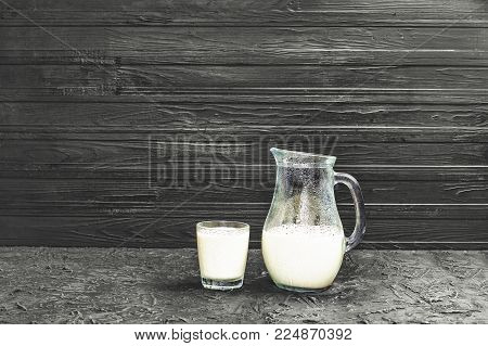 Milk. A jug and a glass of natural cow or goat milk on a black background. Copy space for text or other products.