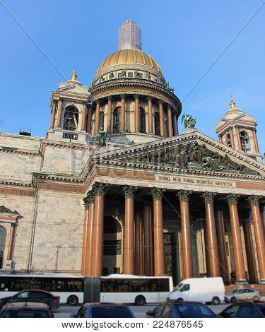 Saint Isaac's Cathedral in St. Petersburg, Russia. Neoclassical Architecture Historical City Landmark Low Angle Street View of Colonnade Pillars and Sculptures against Blue Sky on Sunny Day.