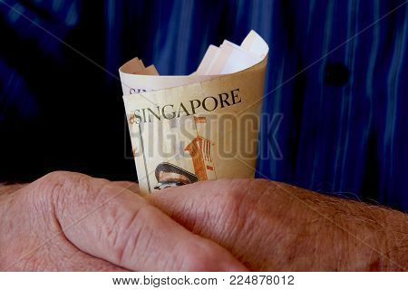 An Old Man Clasping A Bundle Of Singaporean Notes.