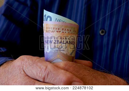 An Old Man Holding A Roll Of New Zealand Dollars.
