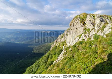 A rocky ledge covered with plants in the Carpathian Mountains. The photo was taken at the end of the day before sunset.
