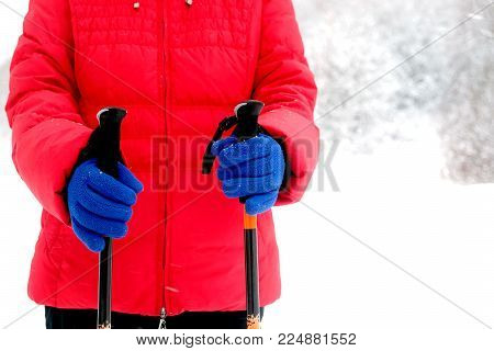 Human in red sport jacket and blue gloves holds two Sticks for hiking in winter season on snow background close up