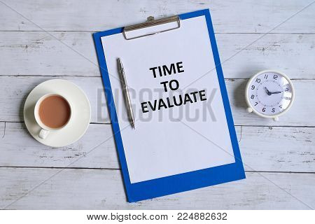 Top view of clipboard with paper written 'TIME TO EVALUATE' with pen,table clock and a cup of coffee on white wooden background.
