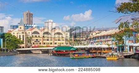 CLARKE QUAY, SINGAPORE - AUGUST 18, 2009: Colorful boats moored at Clarke Quay on the Singapore River with Riverside Point in the background