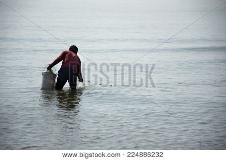 Thai Man Use Fish Net Trap For Fishing In The Sea At Phetchaburi, Thailand