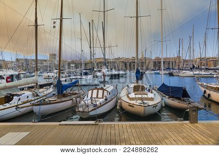 MARSEILLES,FRANCE-AUGUST 10,2016:boats moored in the port of Marseilles in France on a sunny day with a striking sky full of smoke from a nearby fire