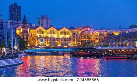 CLARKE QUAY, SINGAPORE - AUGUST 14, 2009: Colorful lights reflected in the Singapore River at night, with Clarke Quay on the right and Riverside Point on the left.
