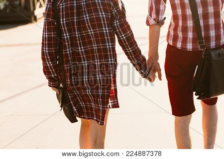 guy and girl in plaid shirt holding hands.