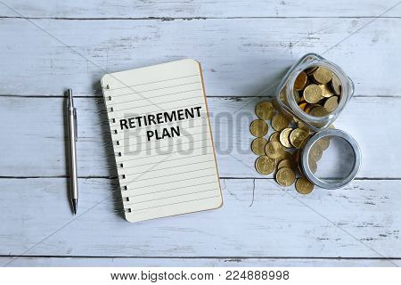 Top view of notebook written with 'RETIREMENT PLAN' with pen and coins on white wooden background.