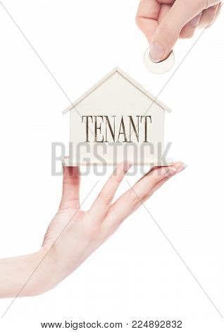 Female hand holds wooden house model and hand holding the coin with conceptual text. Tenant