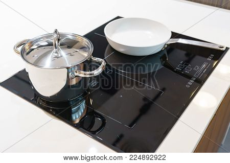 Metal Pot And Pan On Induction Hob In Modern Kitchen. Modern Kitchen Pot Cooking Induction Electrica