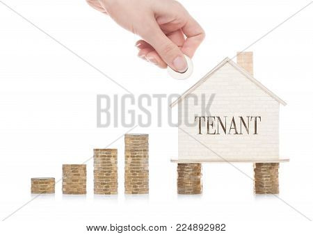Wooden house model standing on coins and hand holding the coin with conceptual text. Tenant