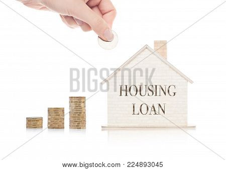 Wooden house model with coins next to it and hand holding the coin with conceptual text. Housing Loan