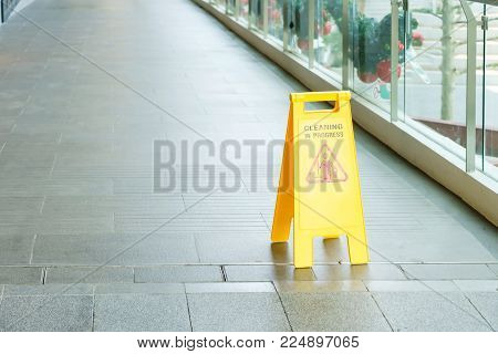 yellow sign inside building hallway, Sign showing warning of caution wet floor, Selective focus